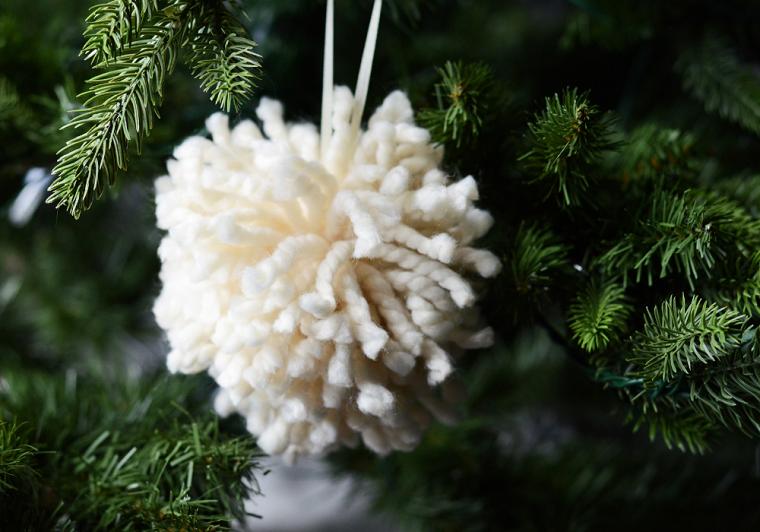 Lavoretti di Natale per bambini, pon pon di filato di lana bianco appeso all'albero