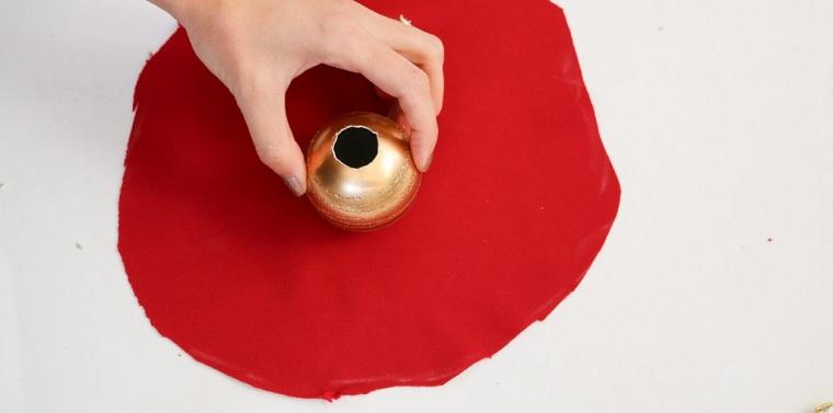 Creazioni di Natale fatte a mano con una pallina e un pezzo di tessuto di colore rosso