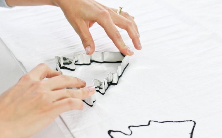 Creazioni di Natale fatte a mano, impronta di vernice forma albero di Natale su un strofinaccio bianco