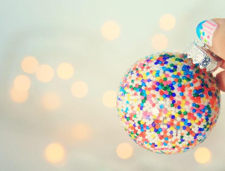 Piccole palline colorate all'interno di una sfera da appendere all'albero natalizio