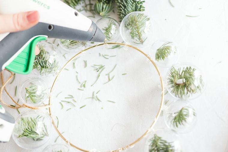 Decori natalizi fai da te, anello di metallo con palline appese e all'interno rametti verdi di pino