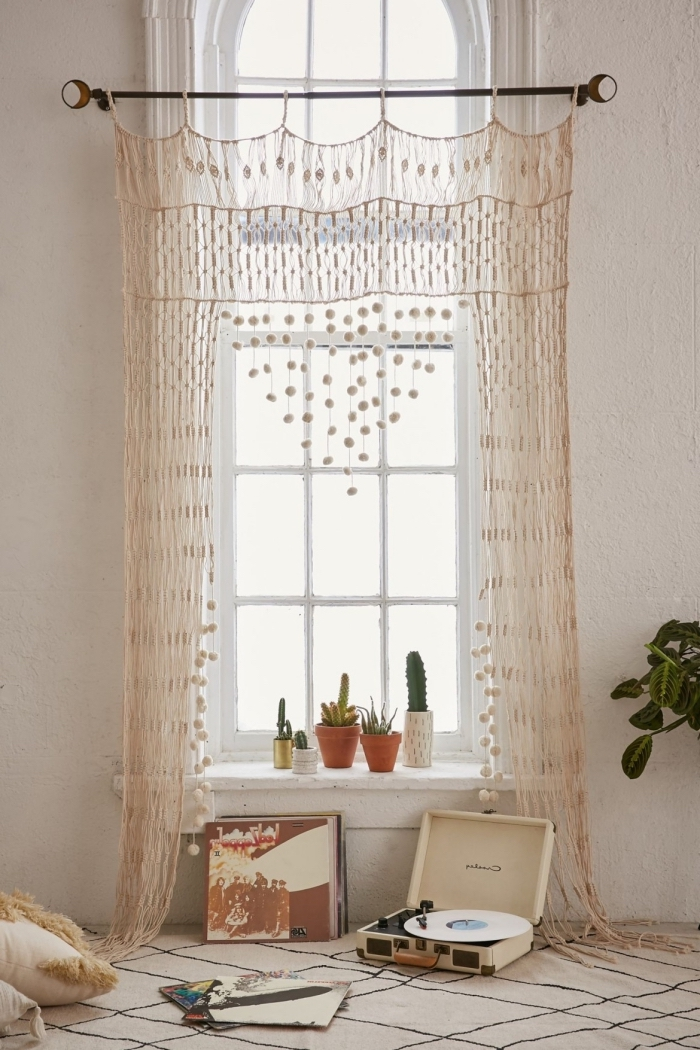 Una finestra con tenda di macramè e bastone di metallo