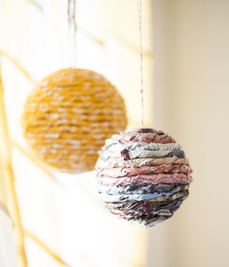 Creazioni di Natale fatte a mano, palline di polistirolo avvolte con strisce di fogli di giornale