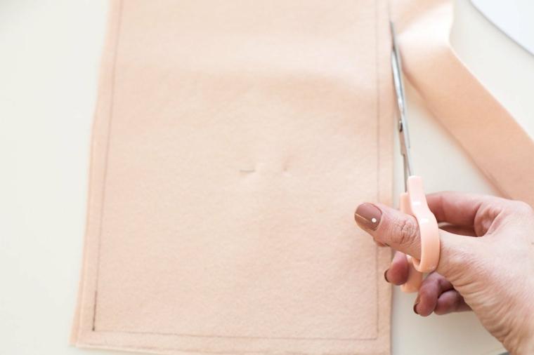Il ritaglio della calza di feltro rosa con forbici, lavoretti creativi Natale con tessuti