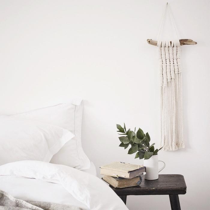 Zona notte con comodino di legno e decorazione fai da te macramè