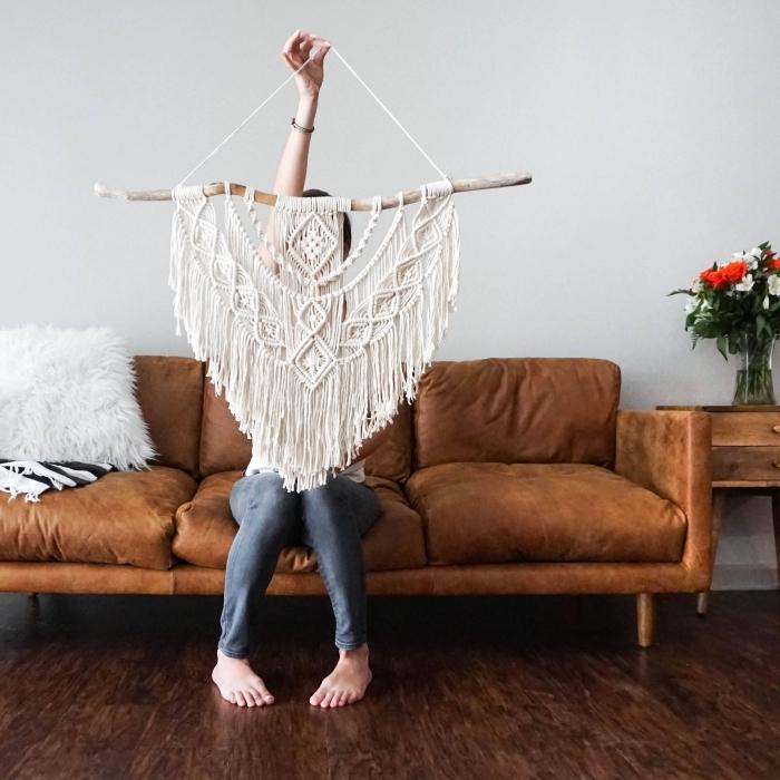 Idea per un macramè a sospensione con corda bianca e pezzo di legno rustico
