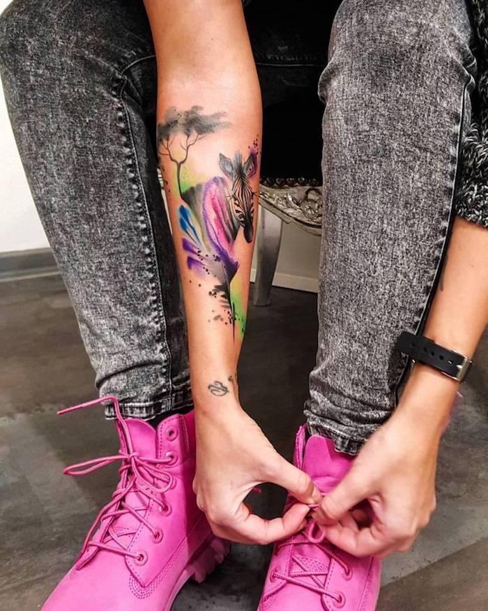 Donna che si lega le scarpe, tattoo colorato di una zebra sull'avambraccio
