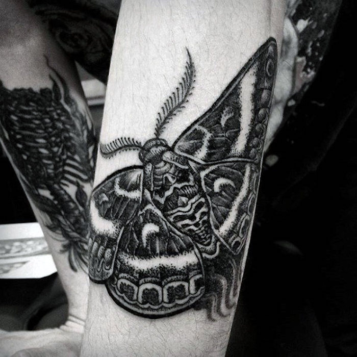 Il braccio di un uomo con piccolo tatuaggio di una farfalla