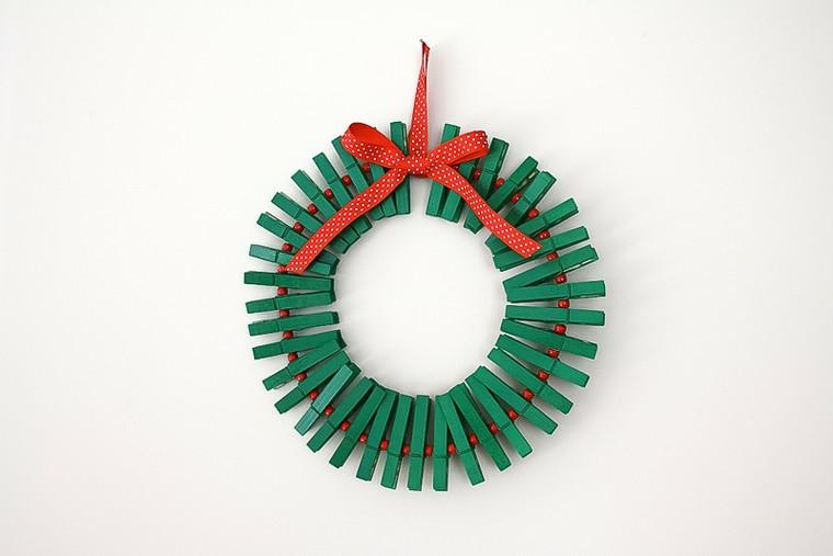 Lavoretti creativi con mollette di legno verde e un nastro rosso da appendere il festone