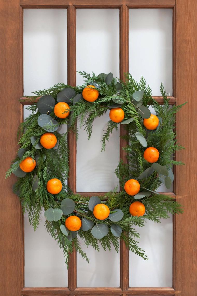 La porta d'ingresso addobbata con una ghirlanda di rametti e clementine