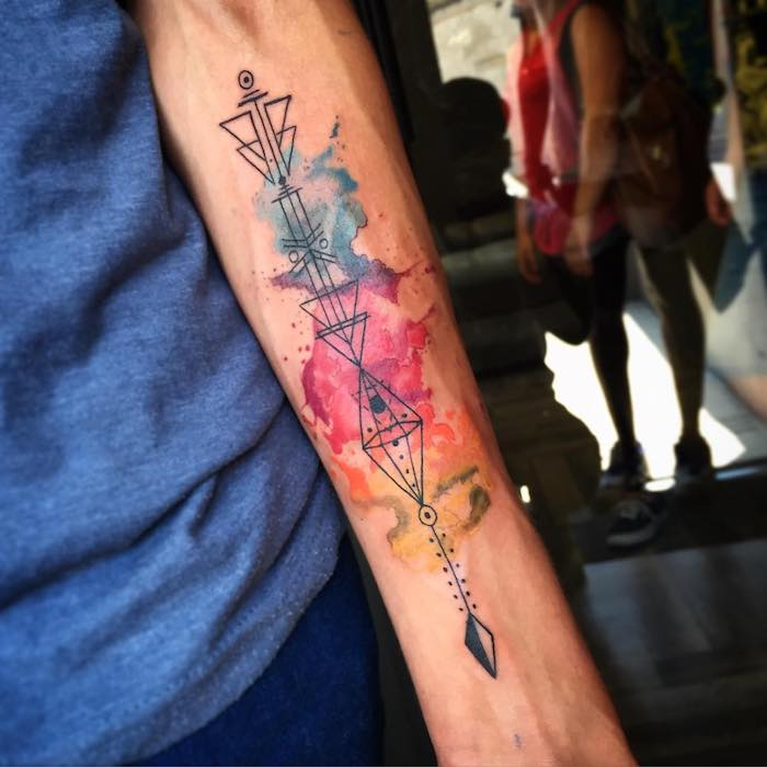 Tatuaggio uomo braccio con forme geometriche e uno sfondo colorato