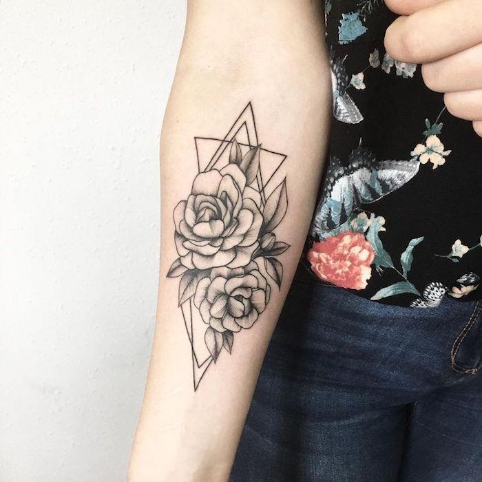 Il braccio di una donna tatuato con un fiore di loto e forme geometriche