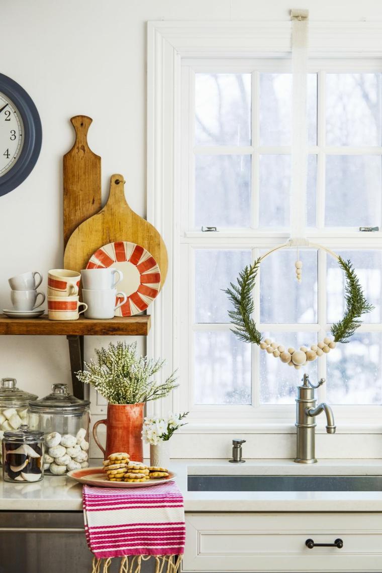 Decori natalizi fai da te con un festone da finestra con palline di legno e rametti