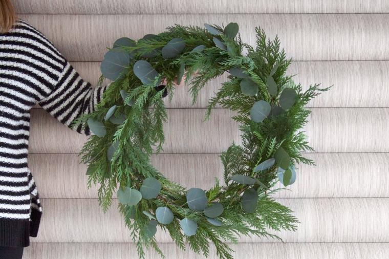 Decori natalizi e un'idea con un festone di foglie e rami dalla forma rotonda