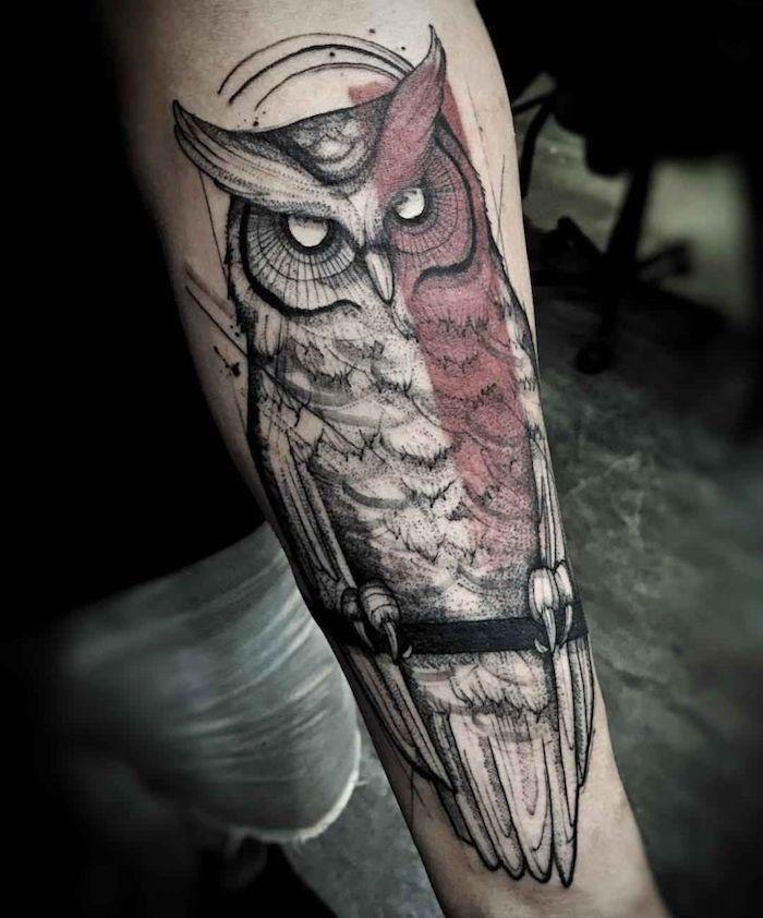Il tattoo colorato di un gufo sull'avambraccio di un uomo