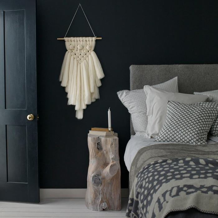 Zona notte con un comodino tronco di legno e decorazione macramè di tessuto bianco