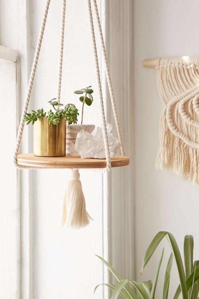 Un addobbo in stile boho chic con pezzo rotondo di legno e piantine sostenute da corde