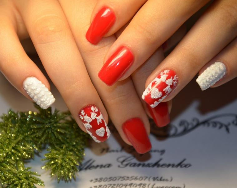 Unghie gel natalizie di colore rosso con disegni bianchi e accent nail effetto tridimensionale