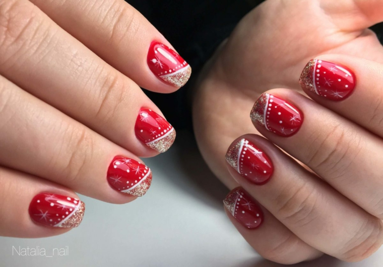 Decorazione unghie rosse natalizie con disegni di smalto bianco e oro glitter