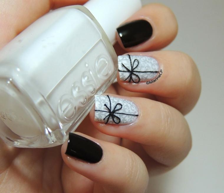 Un'idea per la decorazione delle unghie capodanno con smalto bianco e nero , disegno di un fiocco