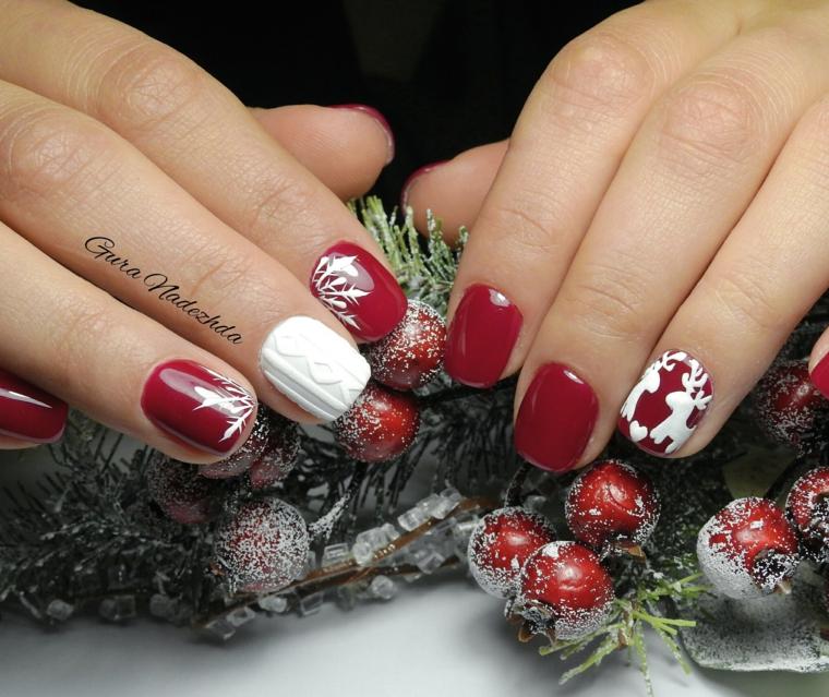 Nail art natalizie con disegni di renne su una base di smalto rosso, accent nails sul dito medio con un bianco
