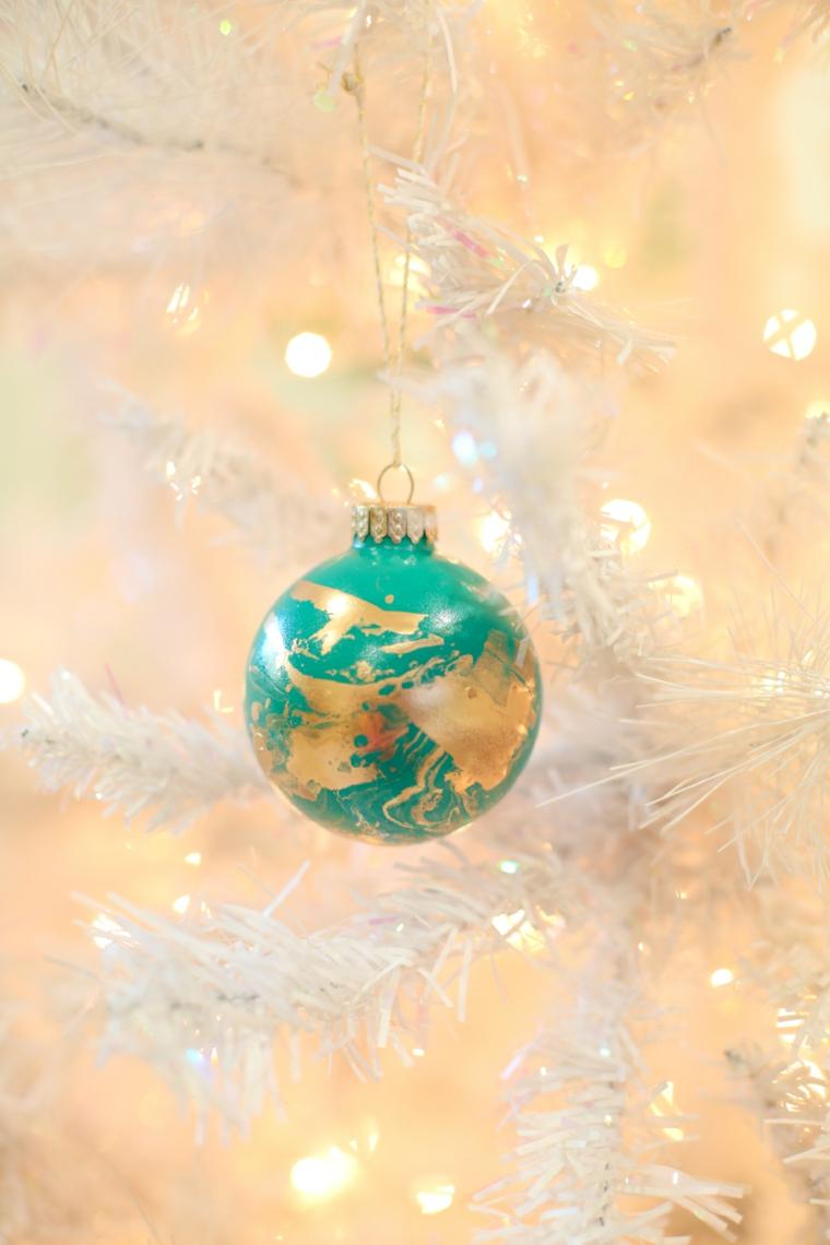 Lavoretti di Natale fai da te facili, pallina colorata di verde appesa su un albero con rami bianchi
