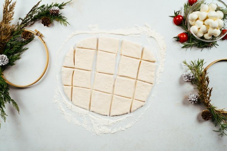 Impasto per pizza tagliato a quadretti, ciotola con baby mozzarella, menu vigilia di Natale