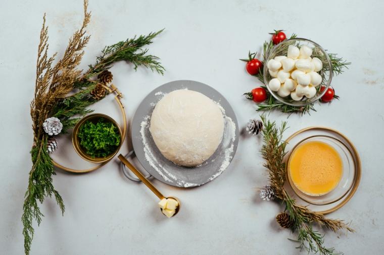 Antipasti vigilia di Natale, ingredienti in ciotole, impasto per pizza, ciotola con baby mozzarella