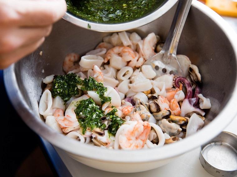 Cena natalizia e un'idea con insalata di frutti di mare in ciotola e salsa verde di erbette