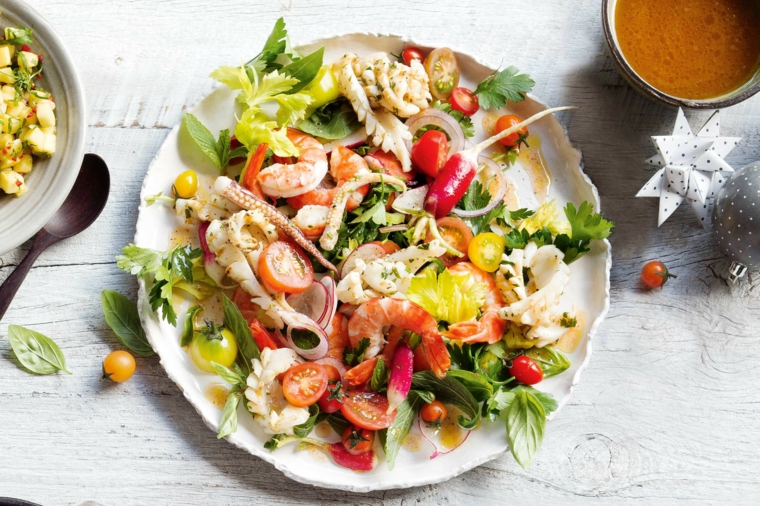Antipasti per la vigilia di Natale e un piatto con insalata di frutti di mare con le verdure