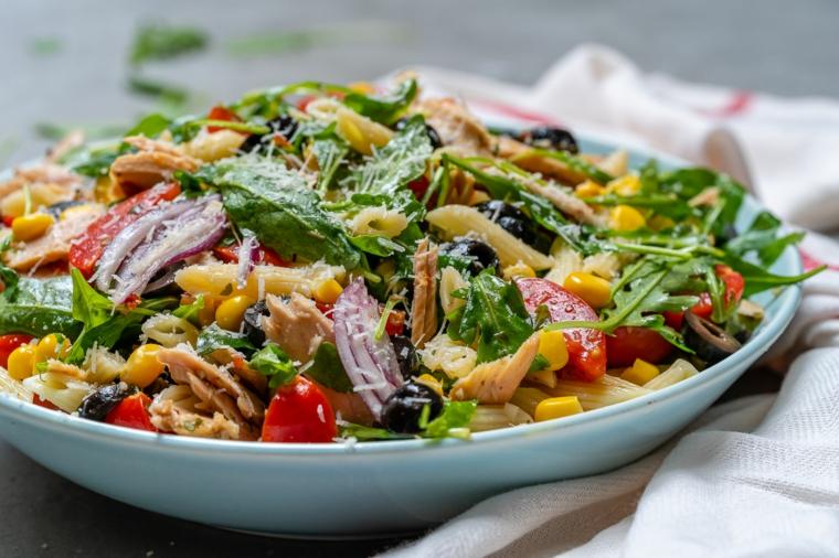 Secondi piatti natalizi di pasta, insalata di penne con verdure fresche e foglie di basilico