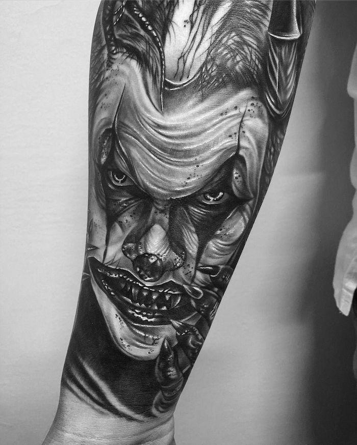Tatuaggio braccio uomo con il disegno del viso di joker con la bocca aperta