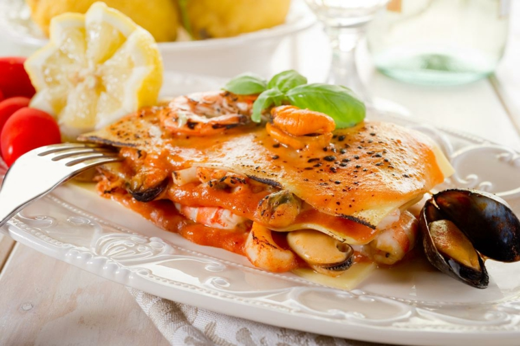 Secondi piatti natalizi di carne e un piatto con lasagna ai frutti di mare e sugo al pomodoro