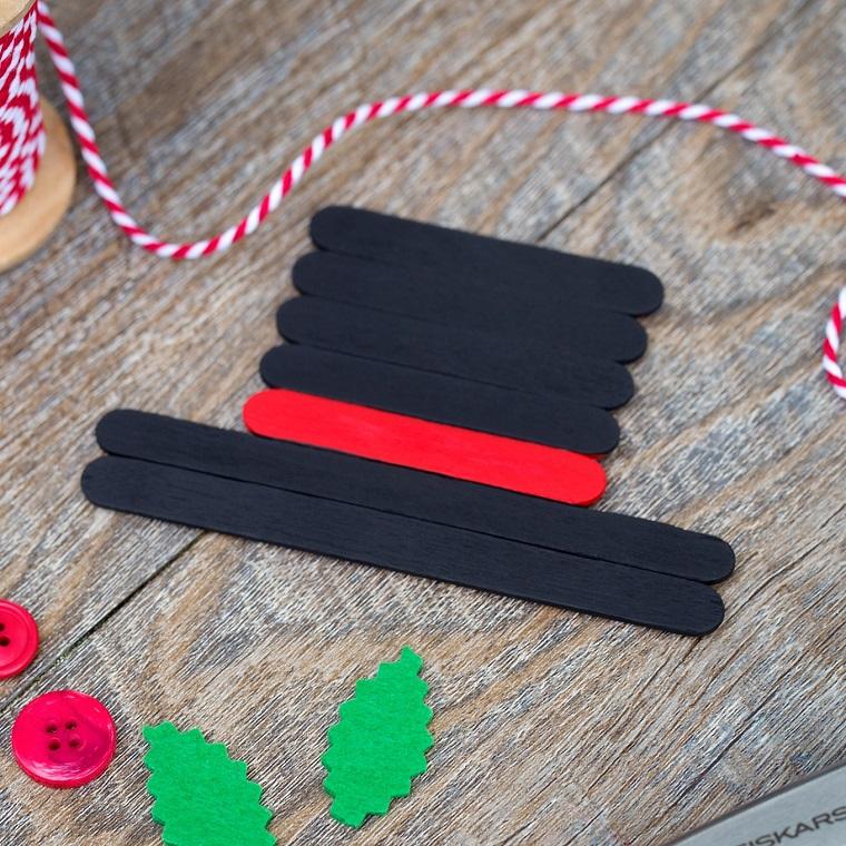 Decorazioni natalizie fai da te con bastoncini di legno dipinti e foglie verdi di feltro