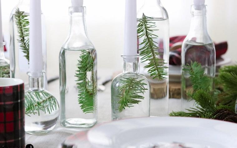 Bottiglie di vetro con acqua e rami all'interno, addobbi natalizi fatti a mano