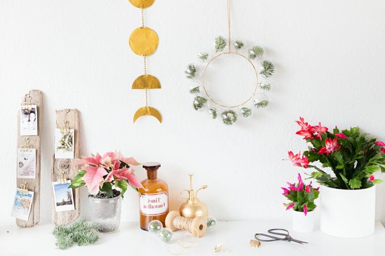 Addobbi natalizi da parete e un'idea con festone di sfere trasparenti con all'interno rametti verdi