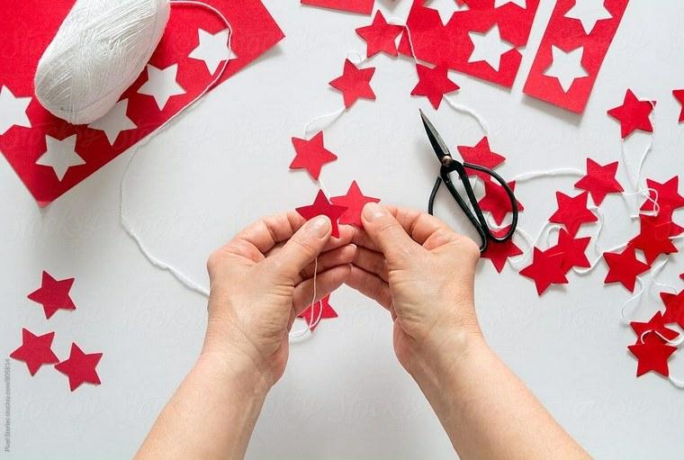 Addobbi natalizi e un'idea con ghirlanda di stelle rosse appese su un filo di lana