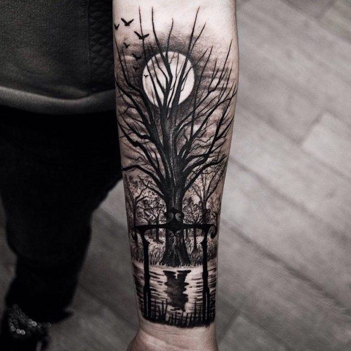 Tatuaggi sulla spalla uomo con il disegno di una foresta al tramonto con albero e lago