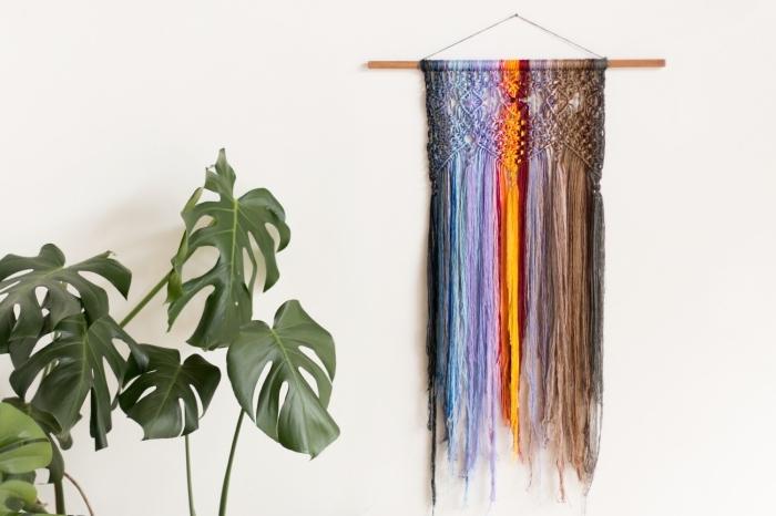 Macramè fai da te con corda colorata attaccato ad una parete bianca su un bastone di legno e chiodo