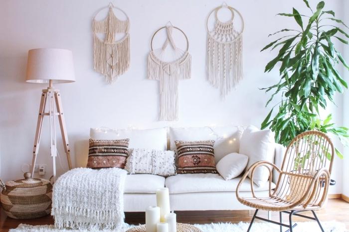 Parete con tre lavoretti macramè di colore bianco e un divano con cuscini