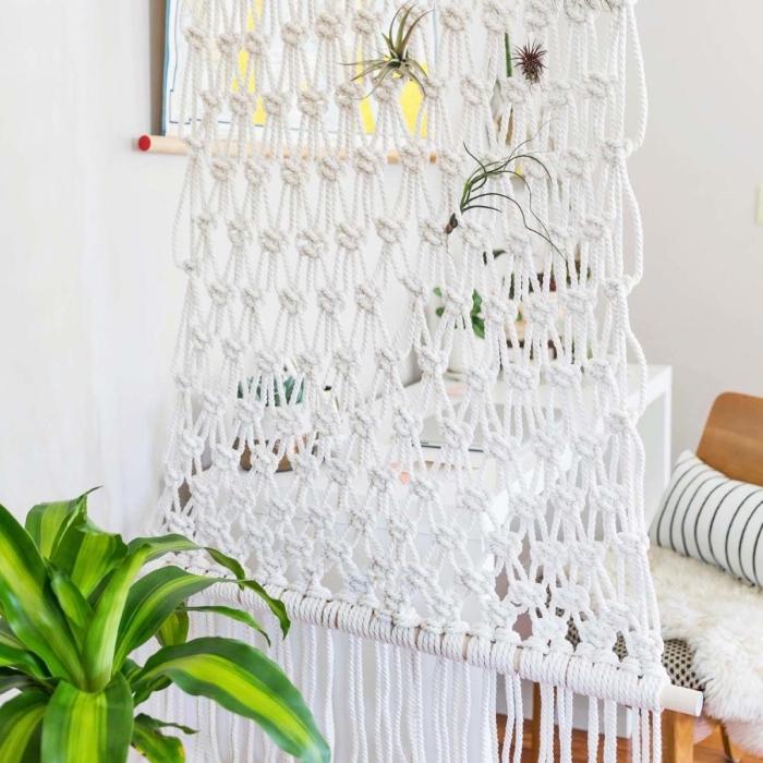 Una stanza con pareti bianche e una decorazione a sospensione di macramè