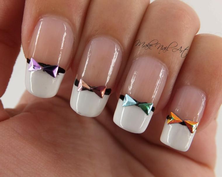 Decorazioni unghie gel con smalto trasparente e french manicure di colore bianco con ornamenti attaccati