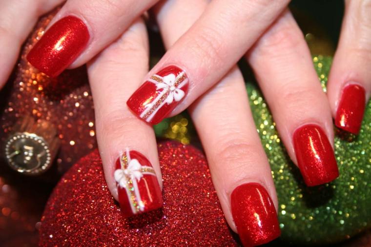 Idea per la decorazione della manicure natalizia con disegno di un fiocco su una base di smalto rosso glitter