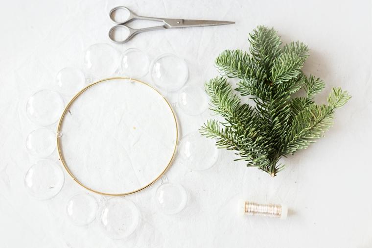 Anello di metallo con sfere trasparenti di plastica, rametti verdi di pino e filo per appendere