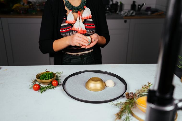 Antipasti vigilia di Natale, palline con ripieno di mozzarella, teglia ricoperta con carta da forno