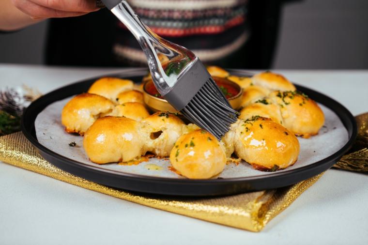 Spennellare il pane con burro, ciotola con salsa di pomodoro, cena della vigilia di natale
