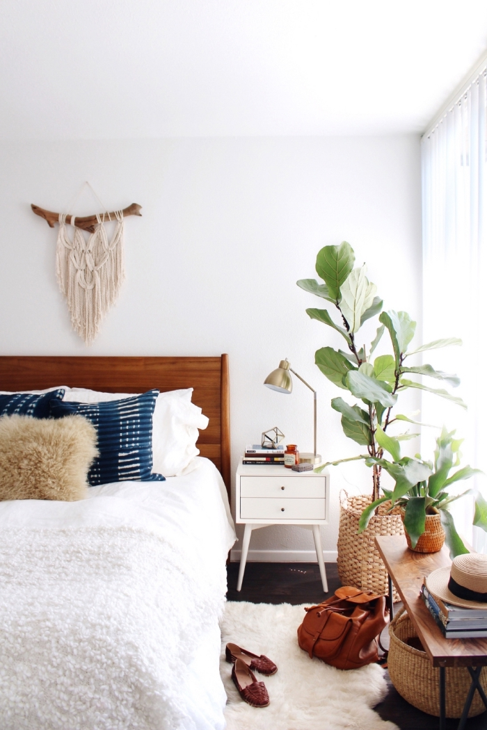 Zona notte con un letto di legno e parete decorata con un piccolo macramè