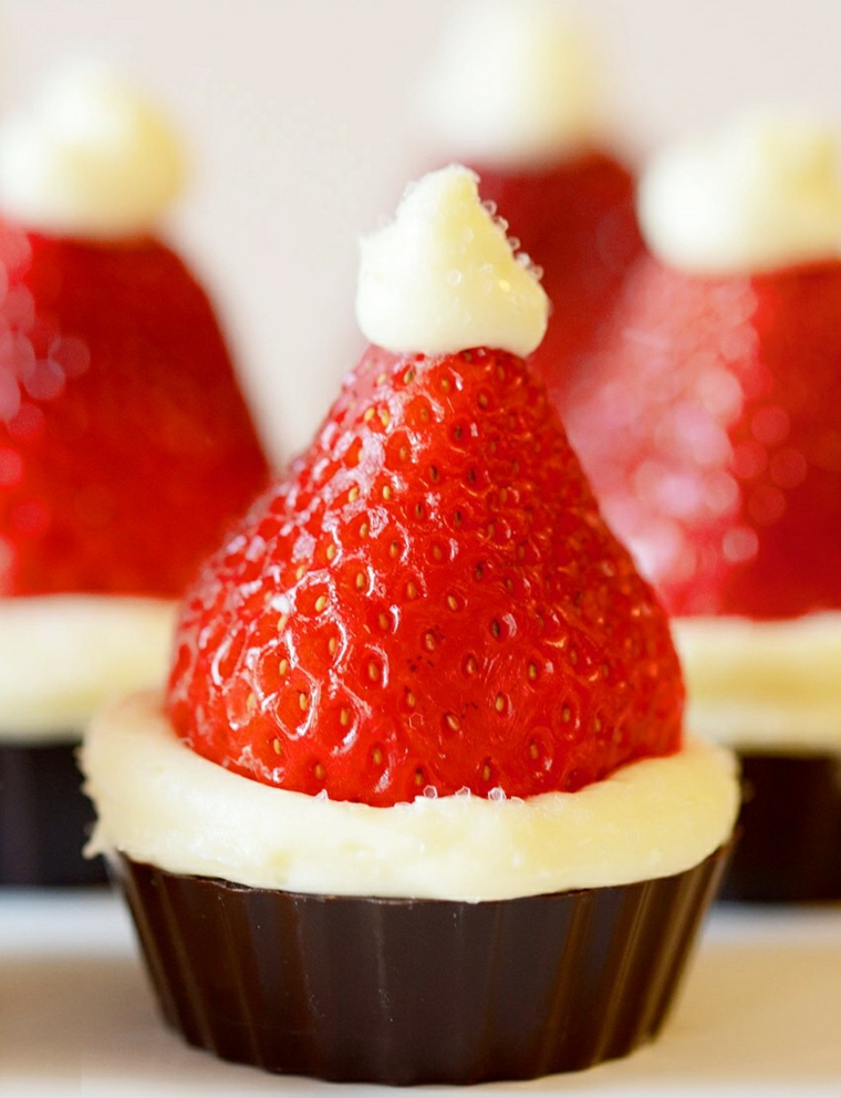 Cheesecake in cestino di cioccolato con fragola e panna montata, dolce natalizio come il cappello di Babbo Natale