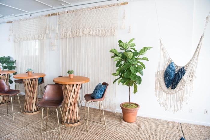 Un soggiorno con tavoli alti di legno e tende in macramè con corda bianca