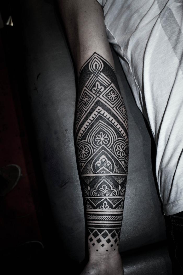 Tatuaggio braccio uomo con disegni e motivi polinesiani
